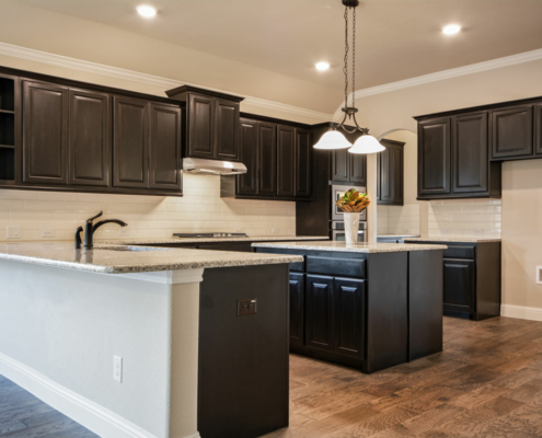 Kitchen cabinets with center island and wood vent and black stain