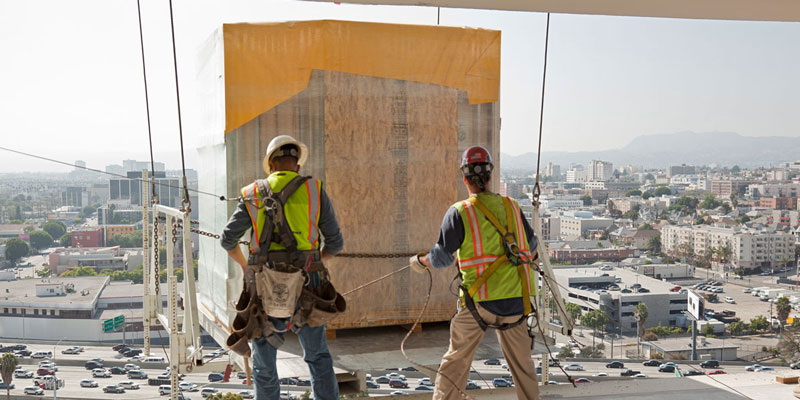 2 workers loading bathroom pod from a crane