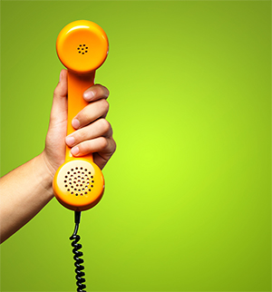 hand holding an old fashioned telephone reciever against a green background