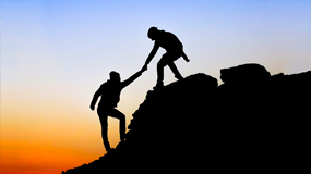 Image of a person helping another person up a hill
