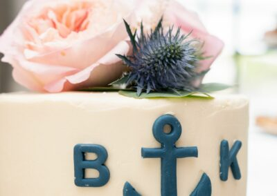 Wedding cake with pink roses and boat anchor, frosting rope and couple's initials.