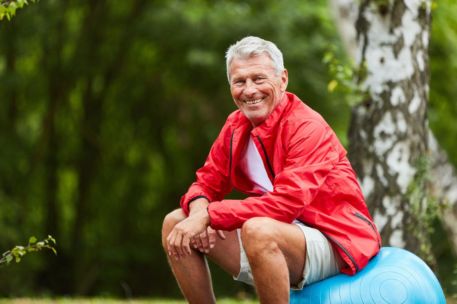 Happy sporty senior man is sitting on a gym ball