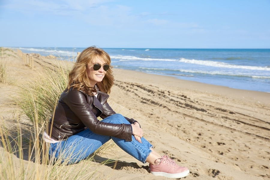 Full length shot of middle aged woman sitting on beach and relaxing.