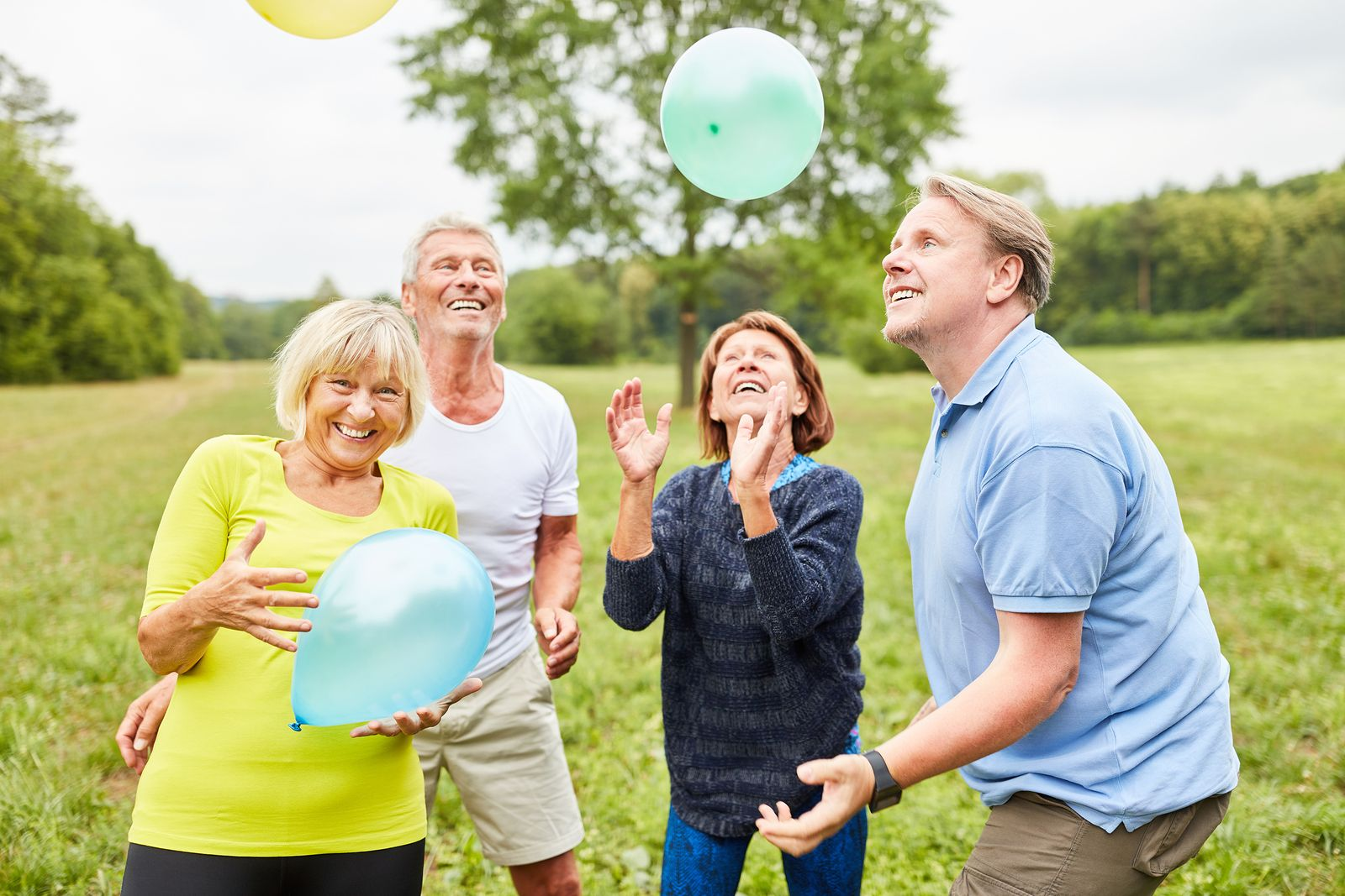 Group of seniors plays with balloons at a party in the park