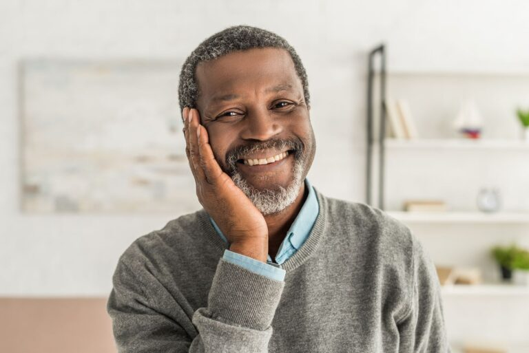 happy african american man holding hand near face while smiling at camera