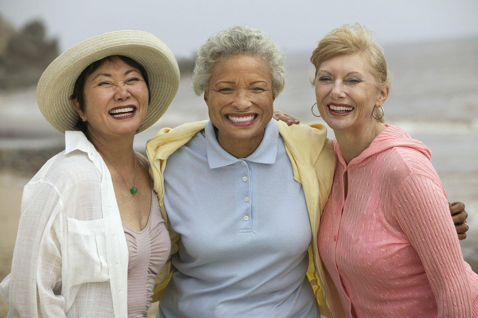Portrait of cheerful female friends enjoying vacation at beach
