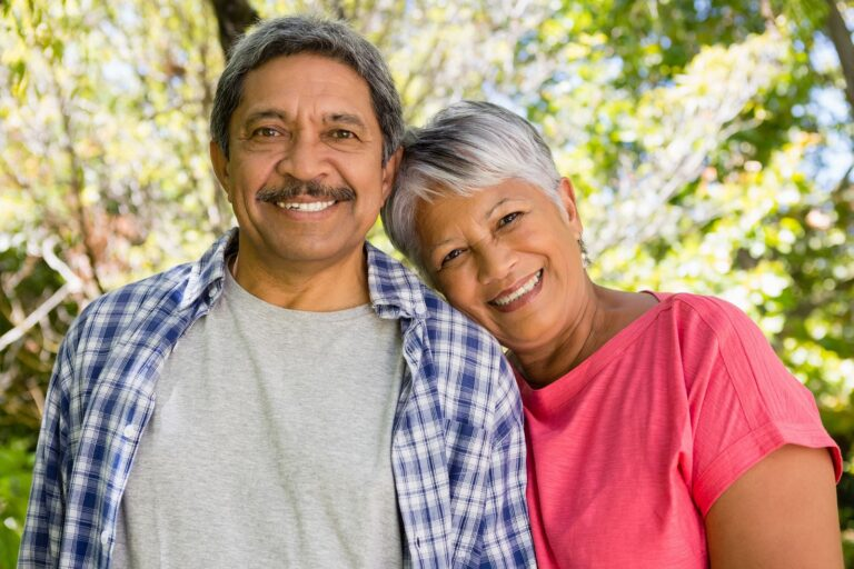 Portrait of smiling senior couple in garden on a sunny day
