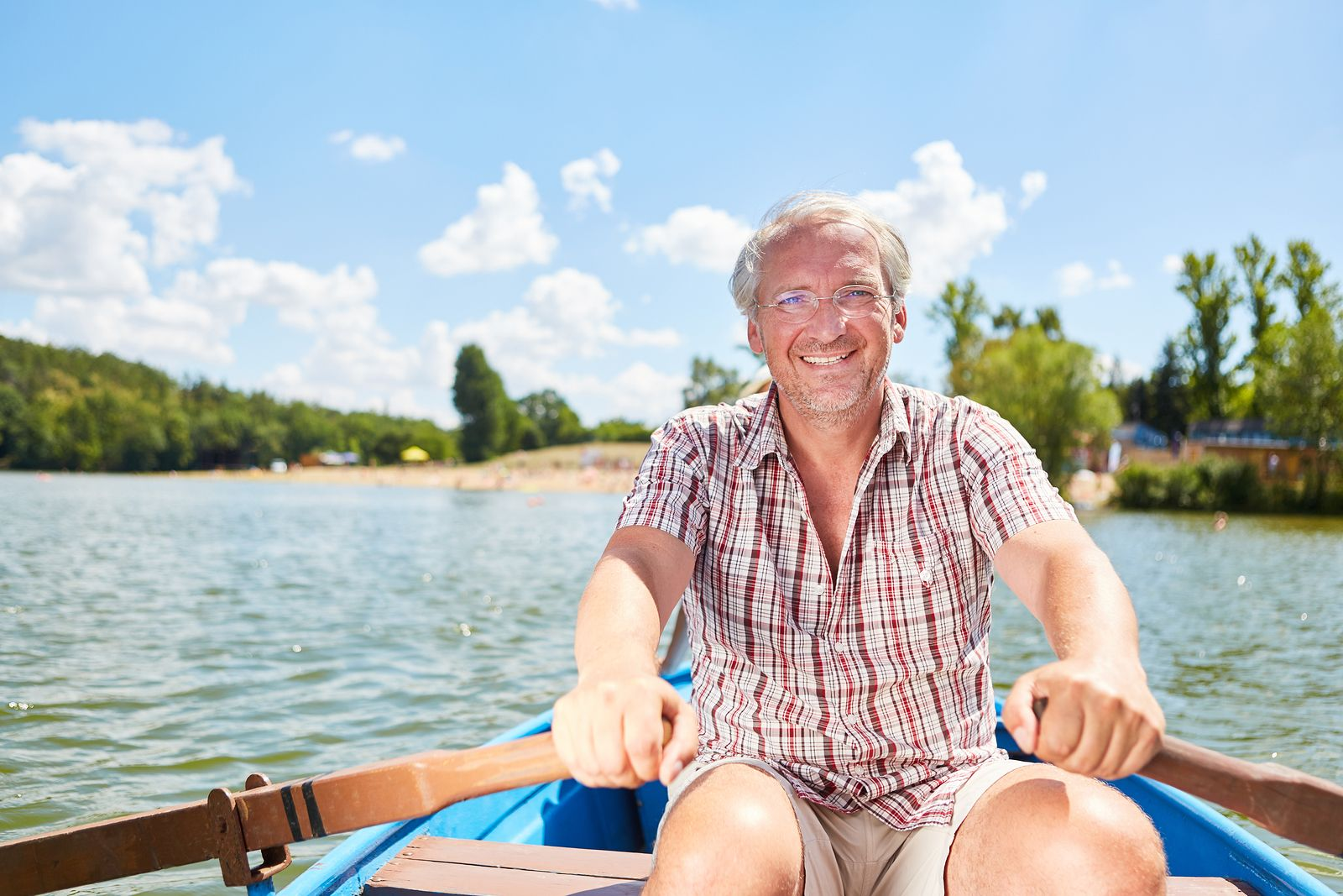 Vital senior man in rowboat on a lake in summer on a weekend