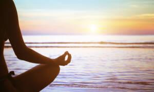 Yogi on the beach practicing mindfulness at sunrise