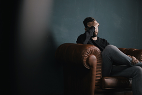 Man on armchair to represent self harm and suicide ideation therapy and counseling