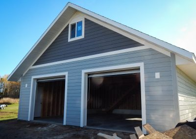 Upgrades Shown: 8/12 Pitch Roof - Storage Truss - LP SmartSide Prefinished Siding - 2′ Overhangs - Aluminum Soffit and Fascia - 9′ x 8′ Garage Doors - 2 J-Blocks- 4′ x 4′ Window - Staircase