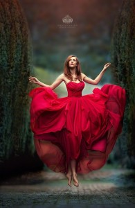 Beautiful woman floating in a red dress.