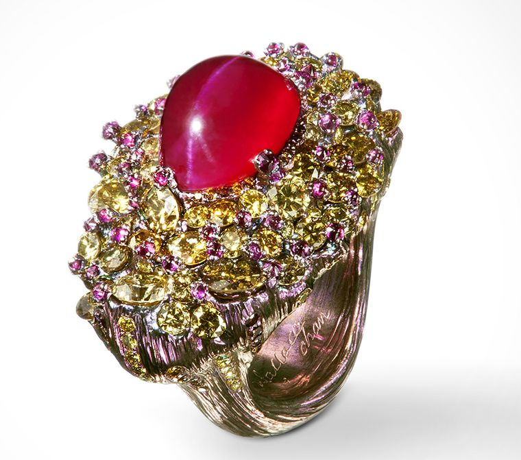 The Beauty of Chaos ring by Wallace Chan speaks of the sometimes random appearance of Nature contrasting with the smooth perfection of the ruby. The 13 Ct cat's eye ruby is surrounded by rubies and fancy colored diamonds. The titanium structure of the ring matches the stones and is in the form of a tree.