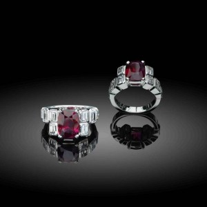 Extravagant art deco-style ruby ring from Star Diamond Private Jeweller featuring a deep red African ruby flanked by emerald-cut diamonds.