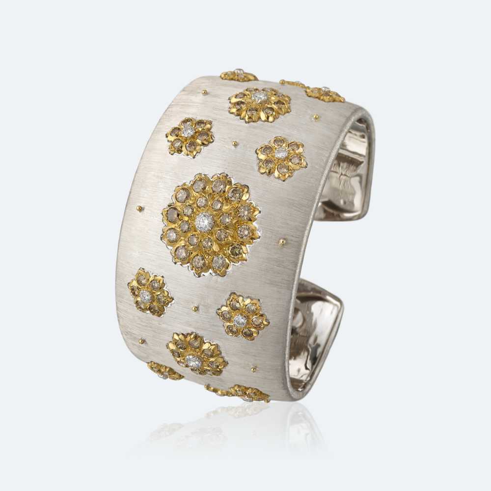 "Cuff bracelet in white gold, ""rigato"" engraved, with yellow gold flowers set with brown diamond, each one centering a yellow gold bezels set with a diamonds. Band width cms. 4,0. 109 round brilliant-cut diamonds cts. 5,45"