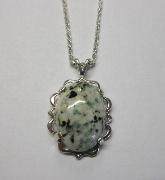 A beautiful custom-cut emerald in matrix mounted in a pendant.