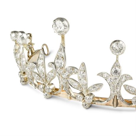A late Victorian diamond tiara, the tiara comprising nine graduated diamond-set fleur de lys motifs with old brilliant-cut diamond tops, alternating with graduating diamond set leaf motifs with diamond trefoils to bottom, all to a gold frame with diamond set scalloped knife edge necklet back, diamonds estimated to weigh a total of 15 carats, set in silver to a yellow gold mount, with hidden side snap clasp, gross weight 65.6 grams, circa 1890.