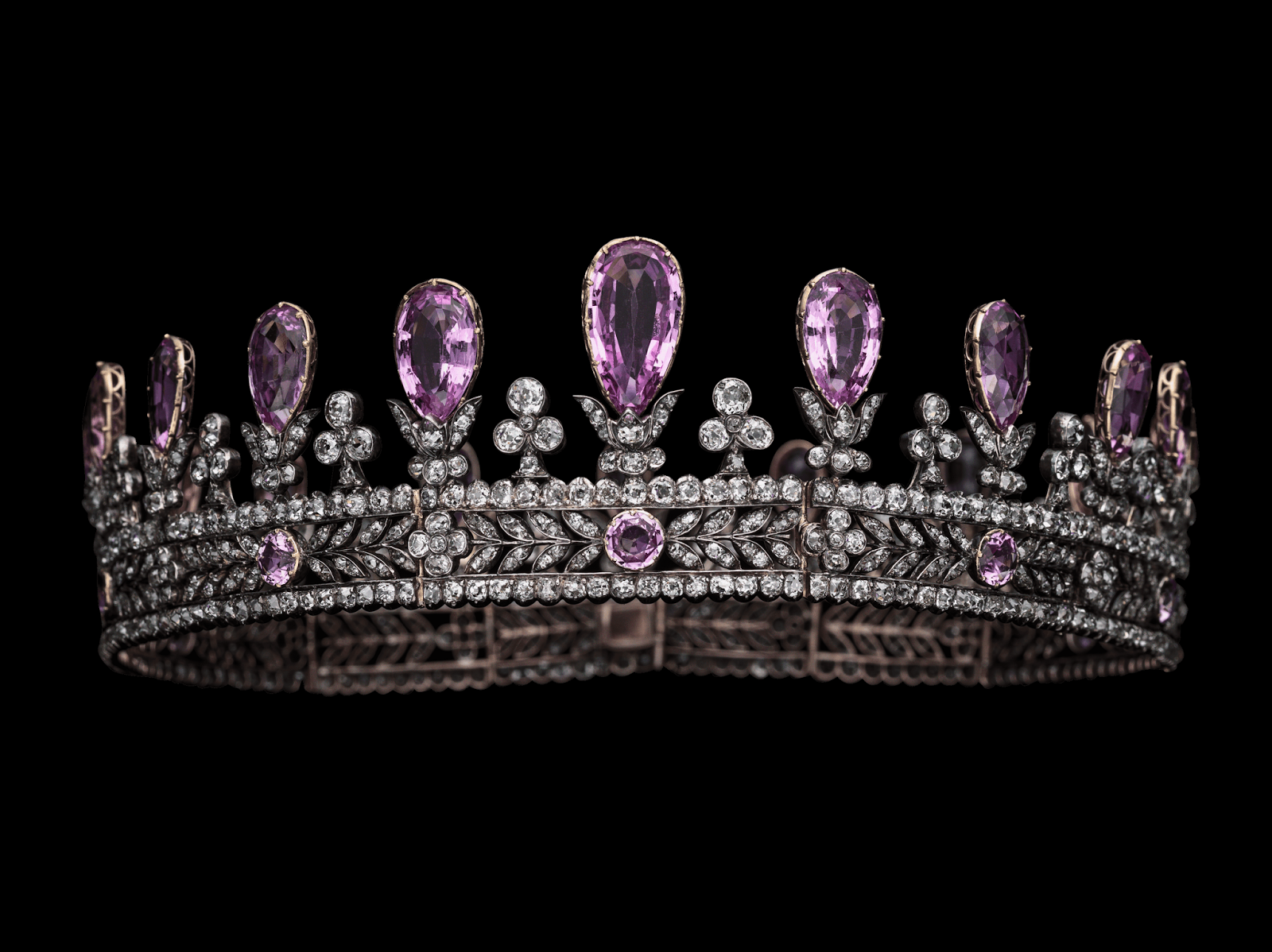Hohenzollern Pink Topaz Tiara: the hinged circlet outlined by a row of collet-set diamonds on the top and lower edges, enclosing circular-cut topazes between diamond leafy branches meeting at diamond quatrefoils, surmounted by a graduated sequence of pear-shaped topazes supported by pairs of old-cut diamond scrolls, alternating with diamond trefoils.