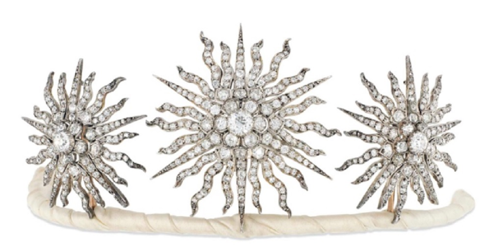 An Edwardian diamond tiara. Designed as a group of three old brilliant-cut diamond graduated sunburst star panels, each with central diamond cluster to a radiating surround of similarly-set rays, mounted in silver and gold, detaching to form three brooches or a hair slide, four additional fittings, circa 1900. Largest star 5.7cm, in fitted case. Sold for £15,000 on 30 November 2016 at Christie's in London