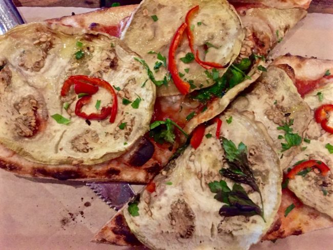 Sicilian Flatbread topped with eggplant, olives, capers, Fresno chilies, and San Marzano tomato sauce