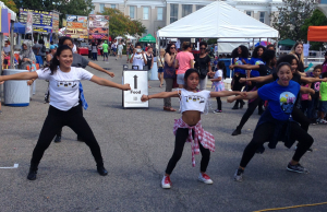 The students in the senior dance company stand in formation waiting for the music to start. The students are performing in front of their non-profit tent for a large crowd at the CenterFest. At the end of the performance spectators cheered and applauded the lively group of young dancers. Photo by Brittney Bizzell / VOICE staff reporter