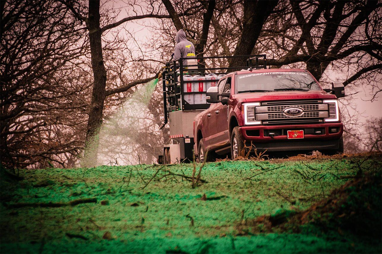 Oklahoma Residential Jobsite-March-2019-Semper Fi Hydroseed spraying in wooded area from trailer with truck in view