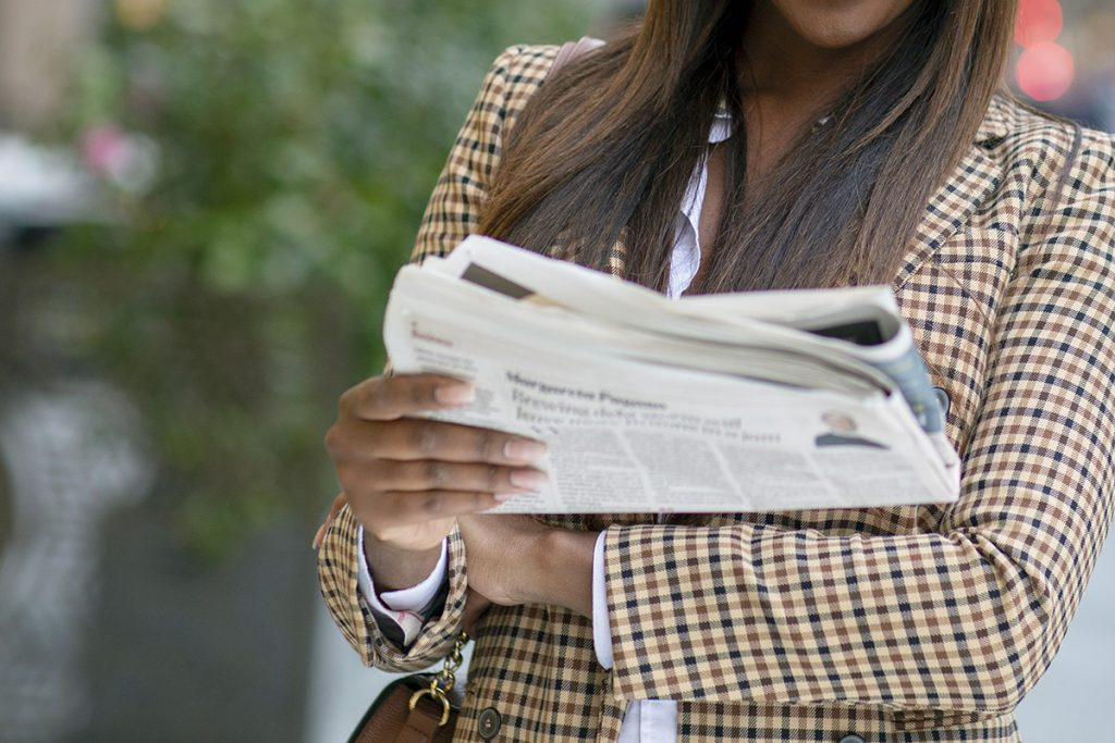 young business woman reading the paper