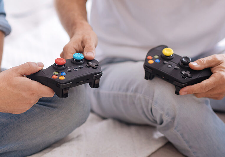 Men like playing game consoles. Black game consoles in hands of two male friends