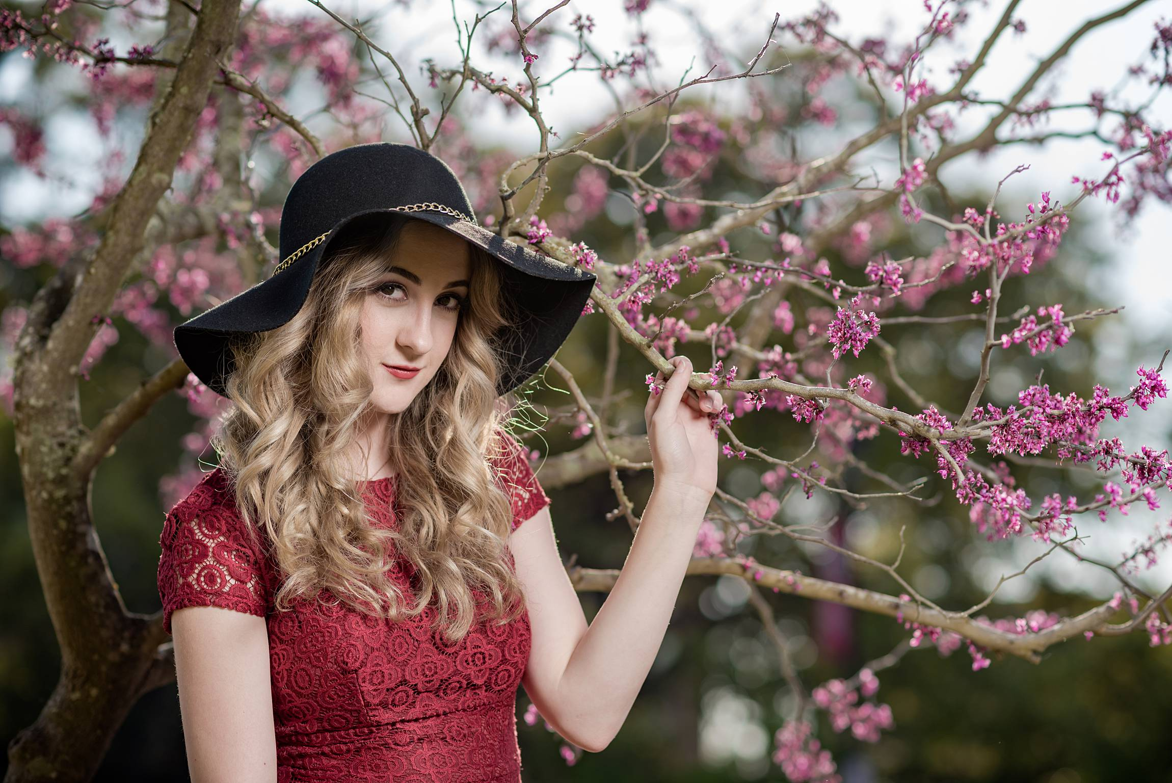 Senior portrait of a girl standing by a tree with purple blooms