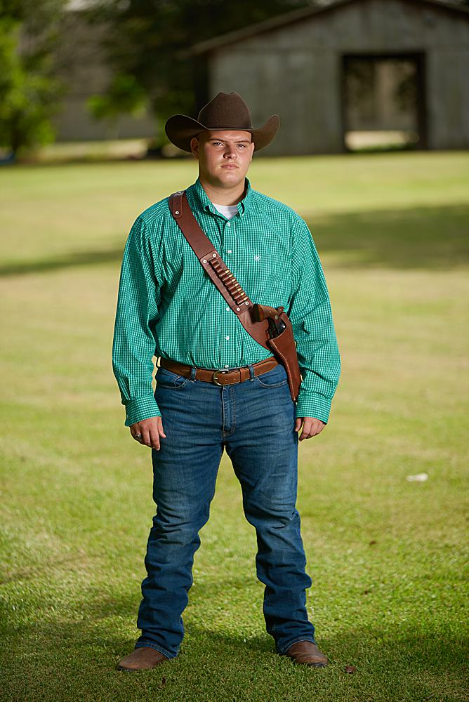 Senior portrait of a young man wearing a cowboy hat and revolver standing in front of a barn