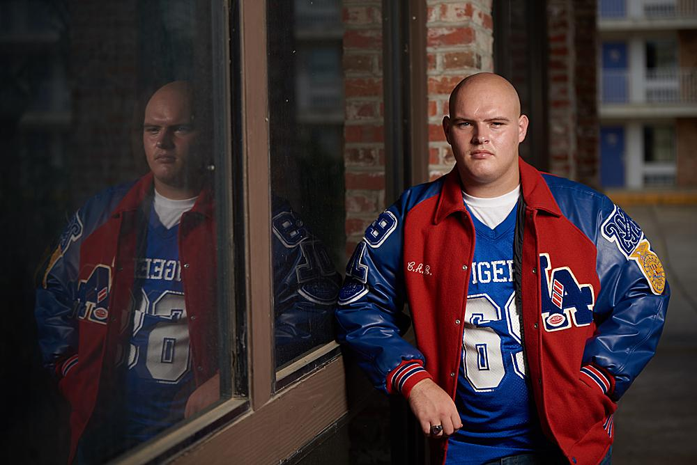 Senior portrait of a young man in a letterman jacket leaning against a window