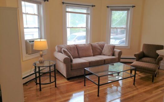 Sun Splashed Living Room With Gleaming Hardwood Floors And Pottery Barn Furnishings.