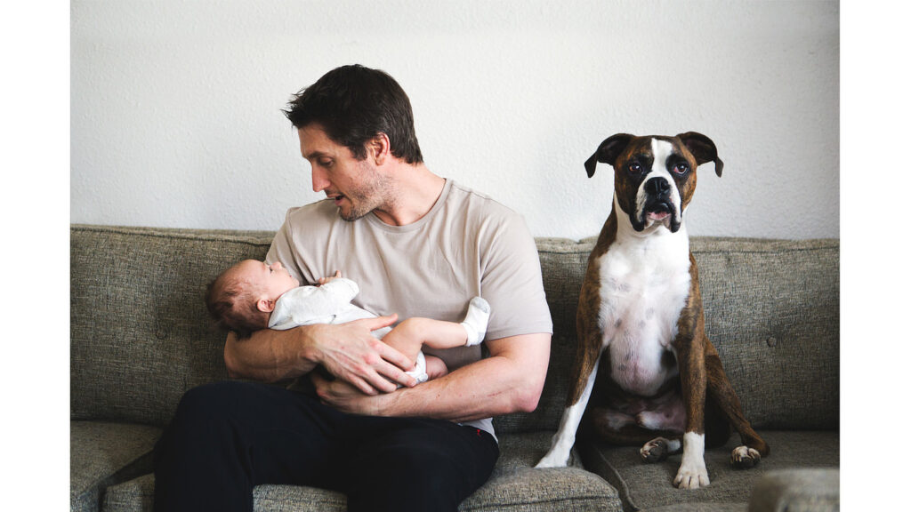 Photo by Heather Gallagher Photography of a man holding a newborn in his arms and dog sitting beside them