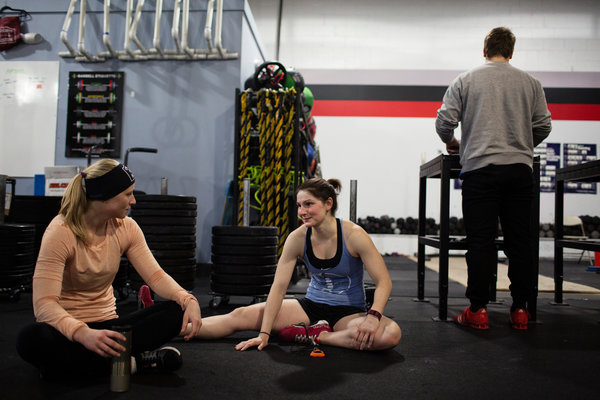 Alex Larcom, left, and Ali Huberlie stretching together at CrossFit Boston. Both women met their partners through the CrossFit community. Photo from New York Times
