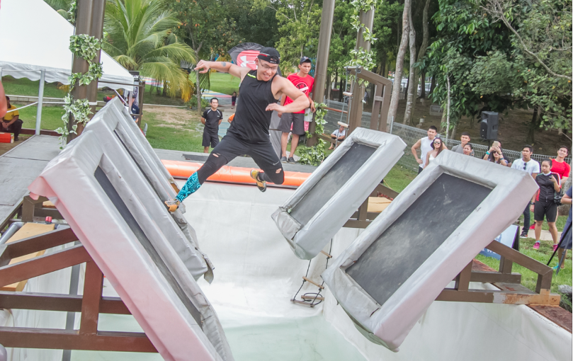 A participant leaps effortlessly across the first obstacle, Chelik Falls