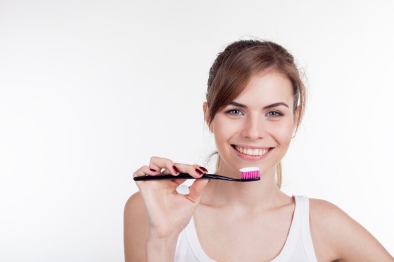 Girl holding a toothbrush with toothpaste on it.