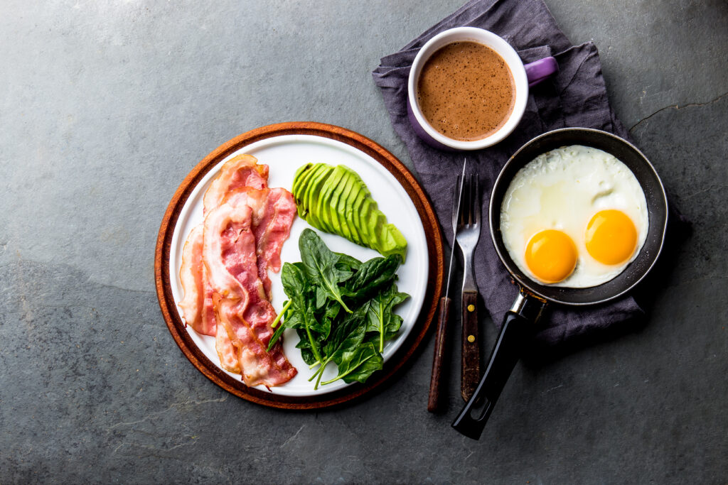 Ketogenic diet breakfast. fried egg, bacon and avocado, spinach and bulletproof coffee. Low carb high fat breakfast.
