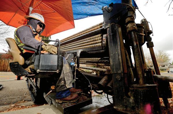 TCS Communications operator Alberto Lucio uses an underground drilling machine to install lines for Longmont's NextLight fiber optic broadband
