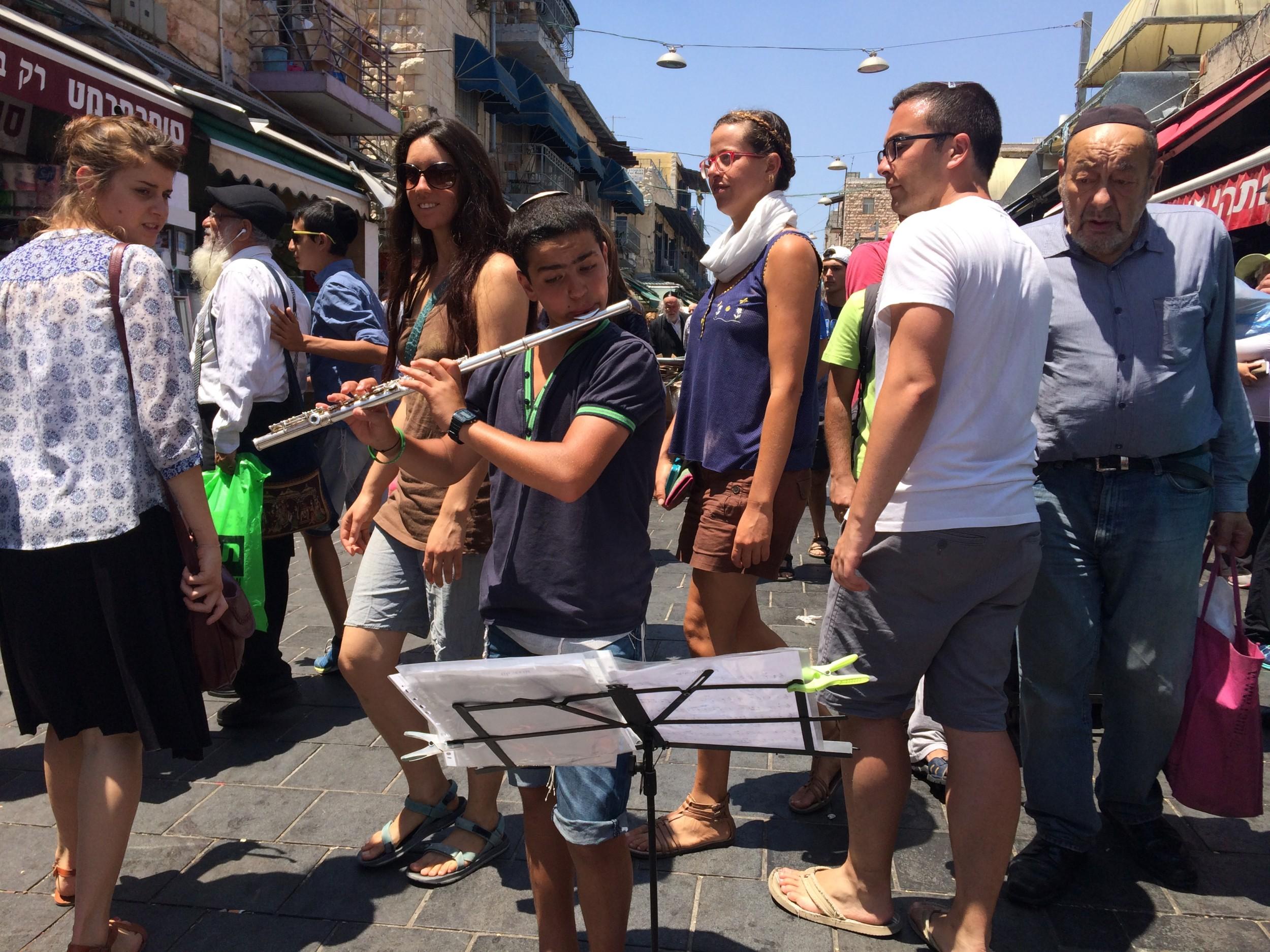 Young flutist in the middle of Jerusalem's shuk, Yehuda Mahane market.