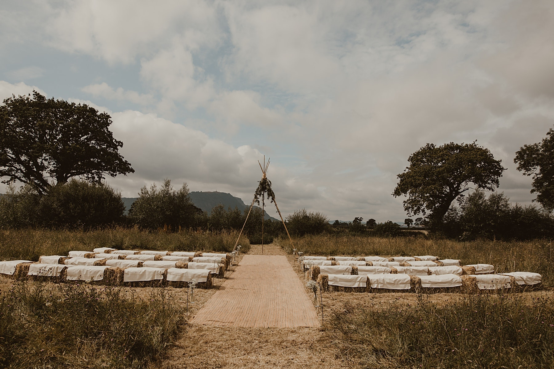 Ceremony tipi in field with hay bales