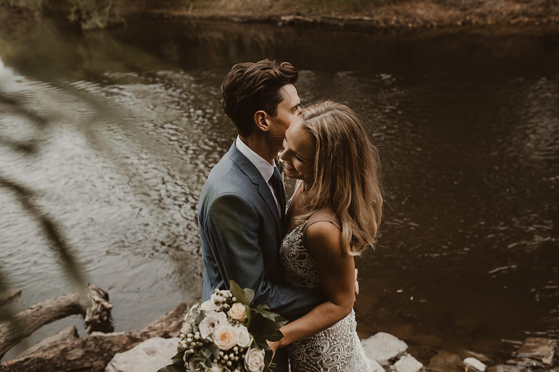 cuddling by a river - relaxed wedding photography