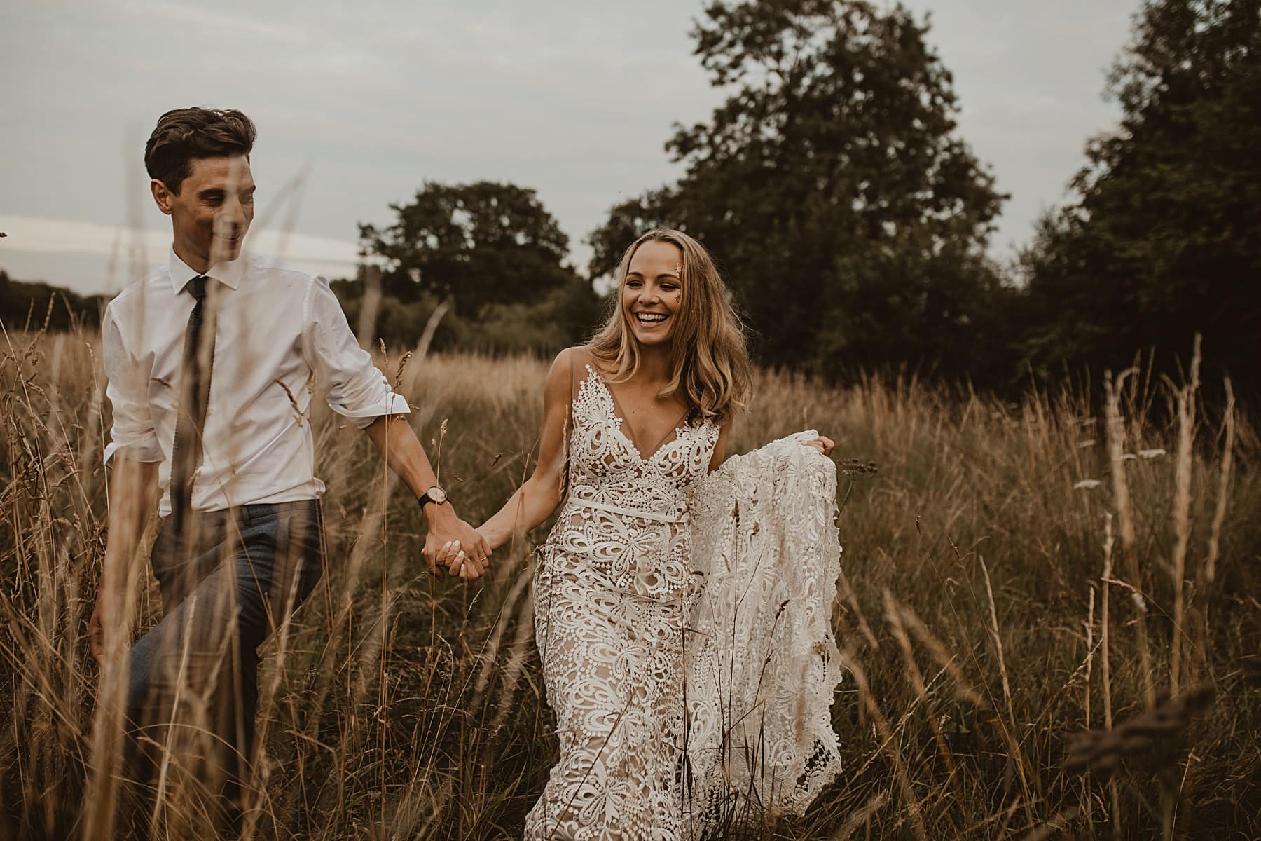 Bride and Groom laughing and walking through meadow