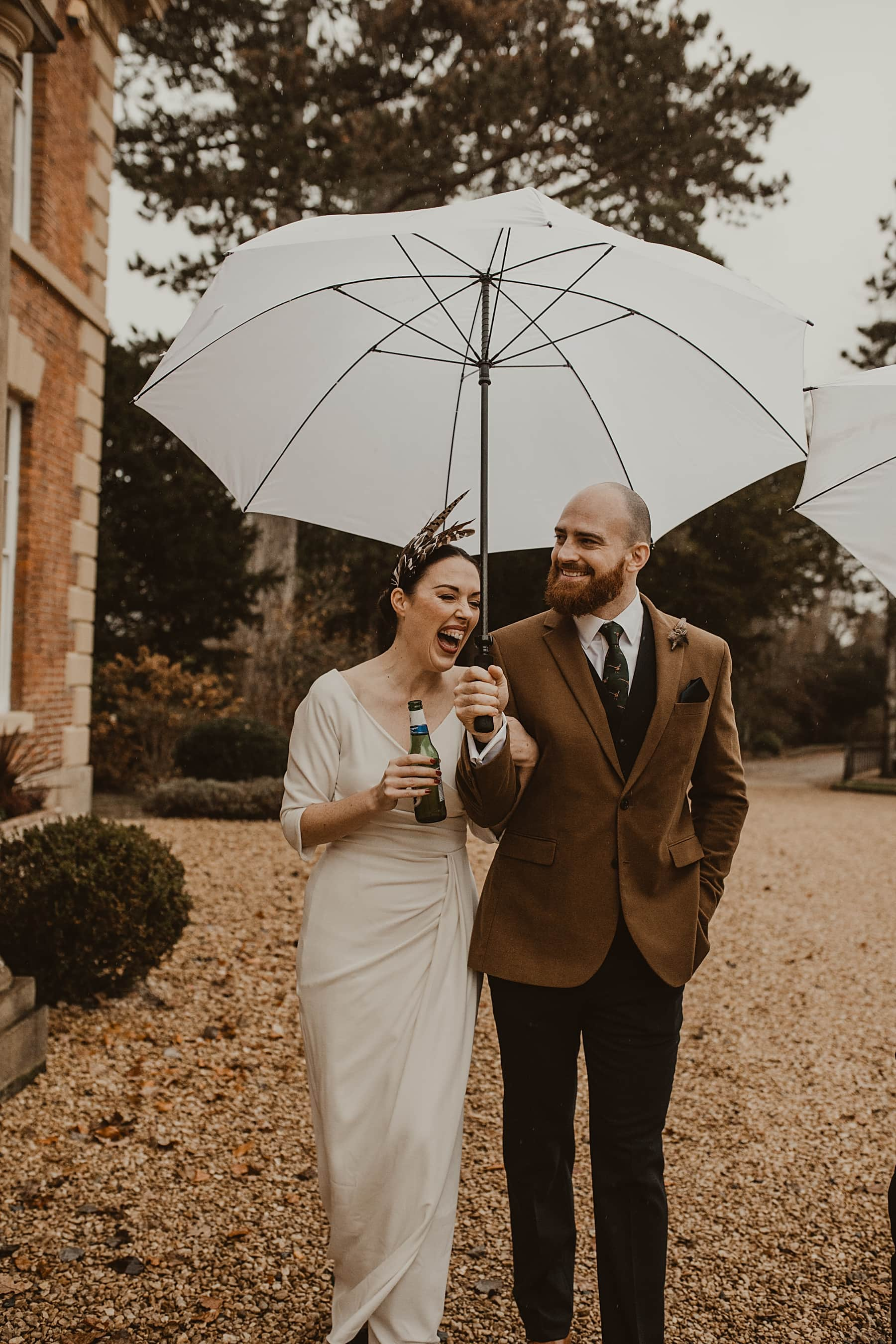 Bride and groom walking in rain