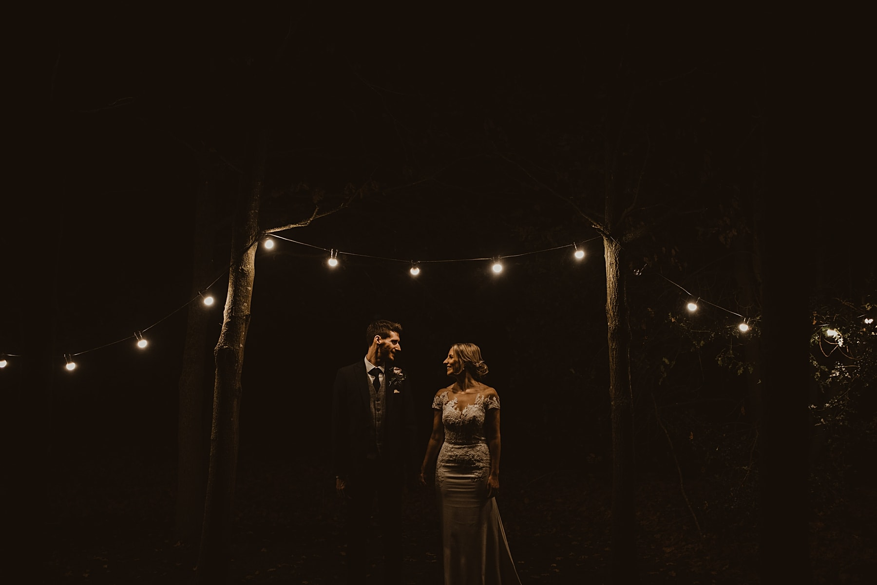Couple standing under festoon lights