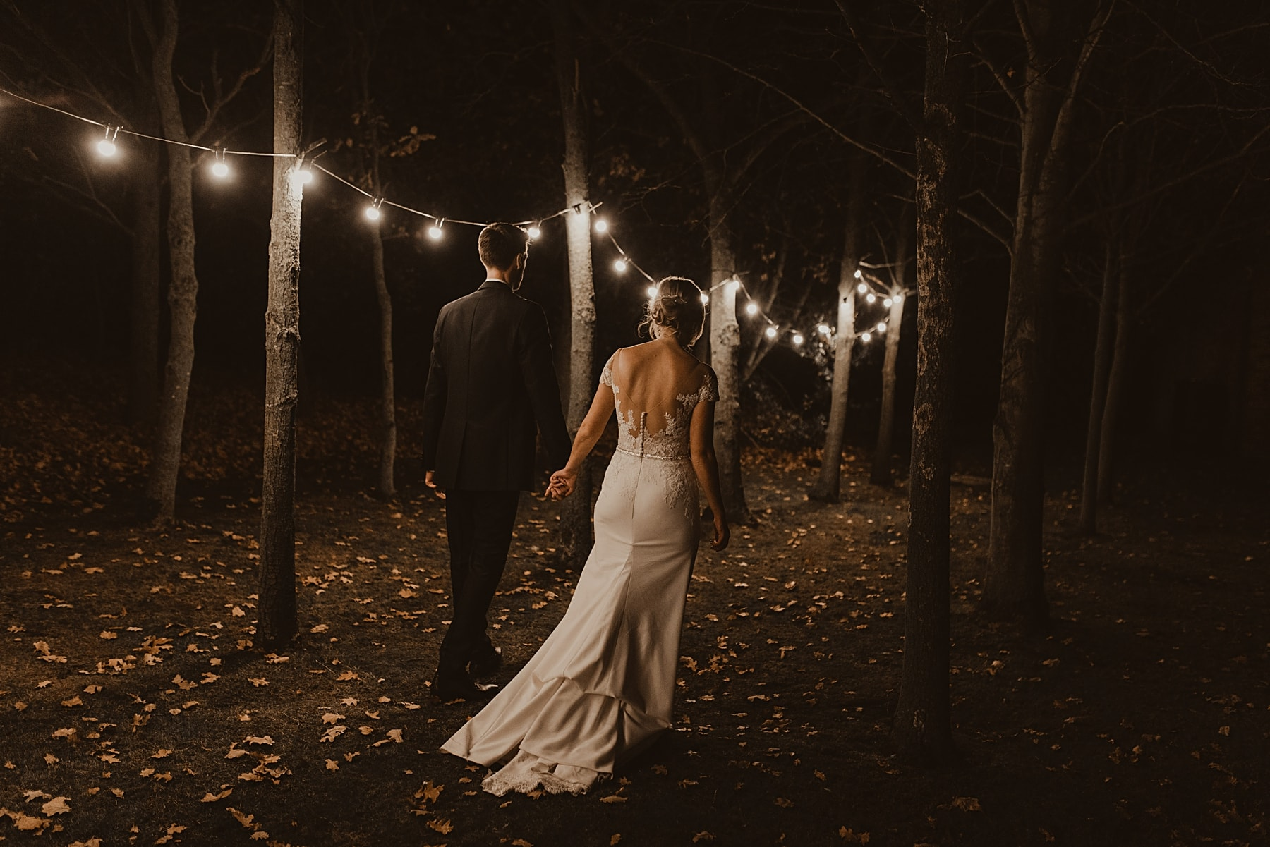 bride and groom walking through woods