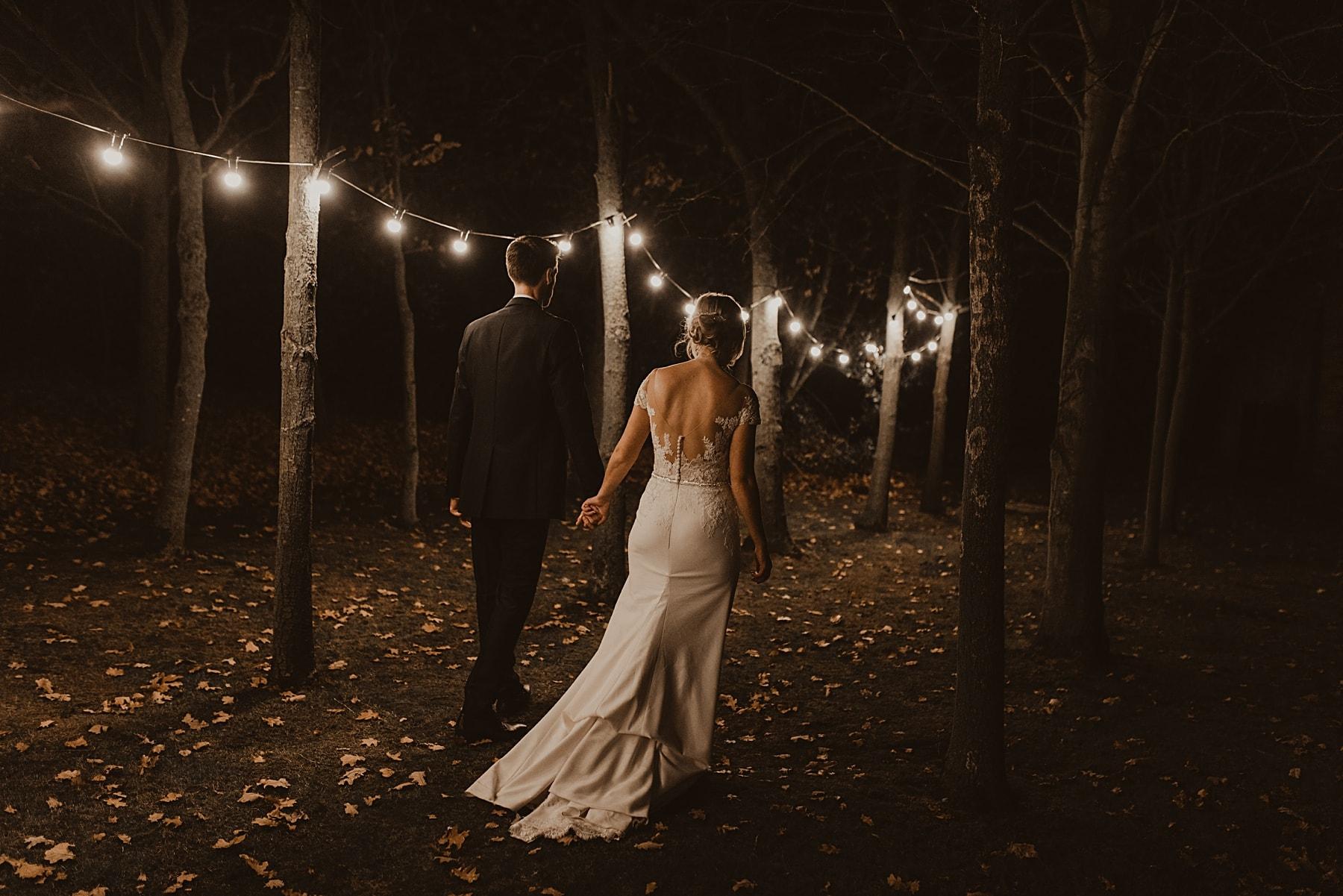 bride and groom walking through woods