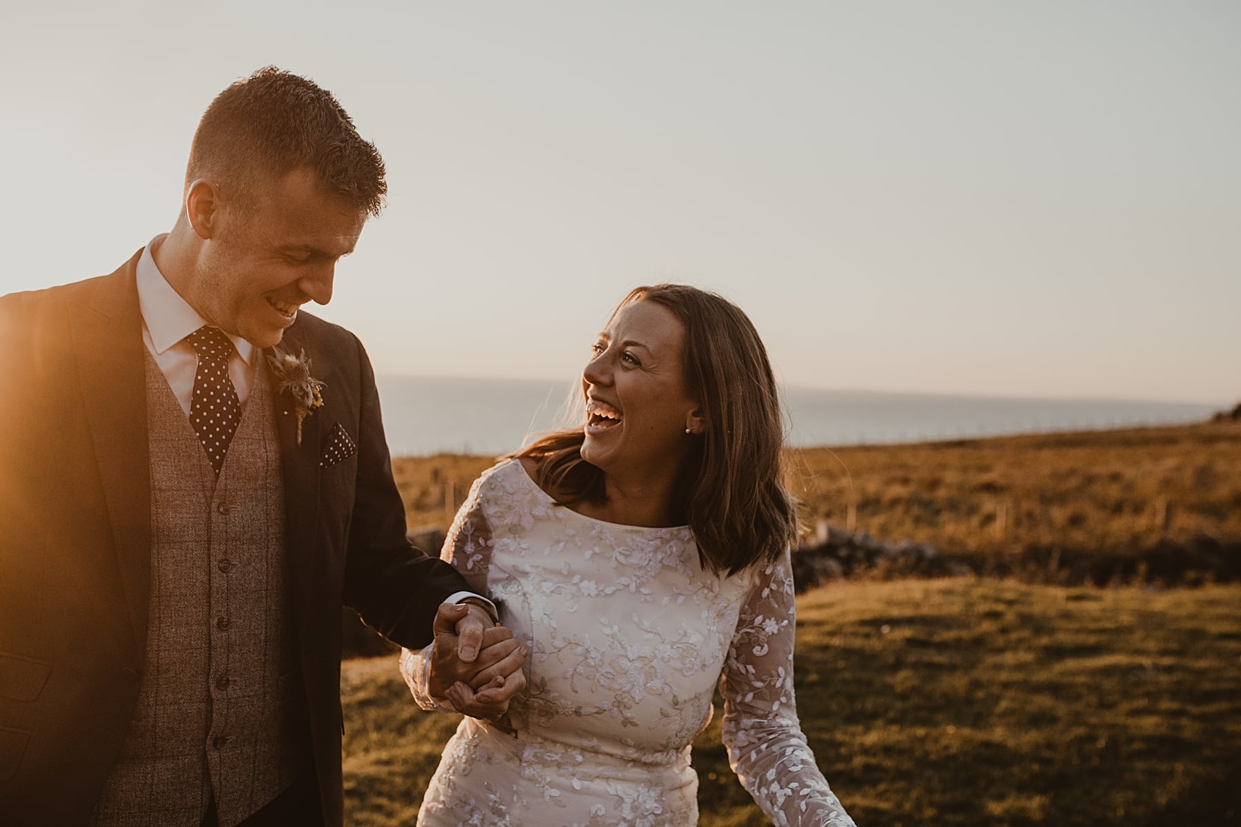 Bride and groom laughing with sunset at Nant Gwrtheyrn