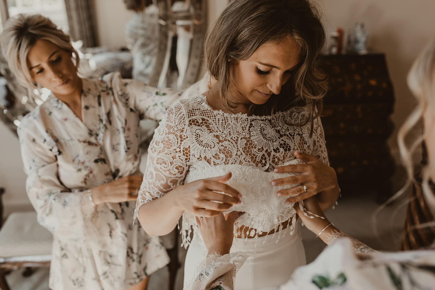 Bride putting two piece, lace wedding dress on