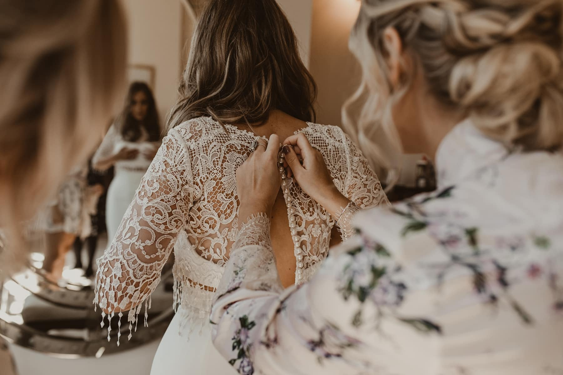 Bridesmaid doing up lace wedding dress