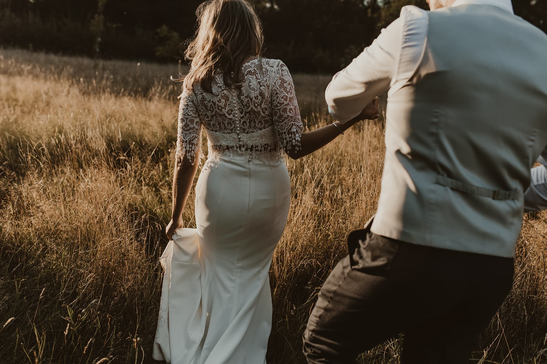 bride and groom walking through meadow during sunset